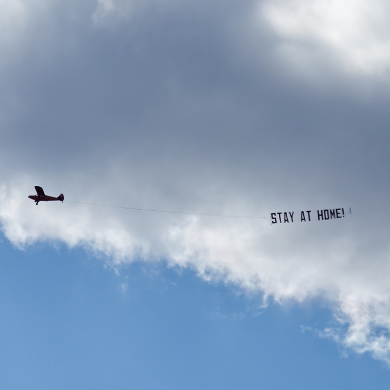 "airplane flying and towing a sign behind it that says ""stay at home"""