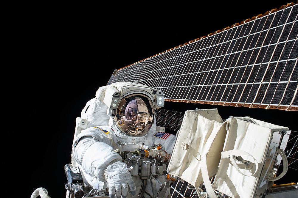astronaut performing maintenance on space craft while in space